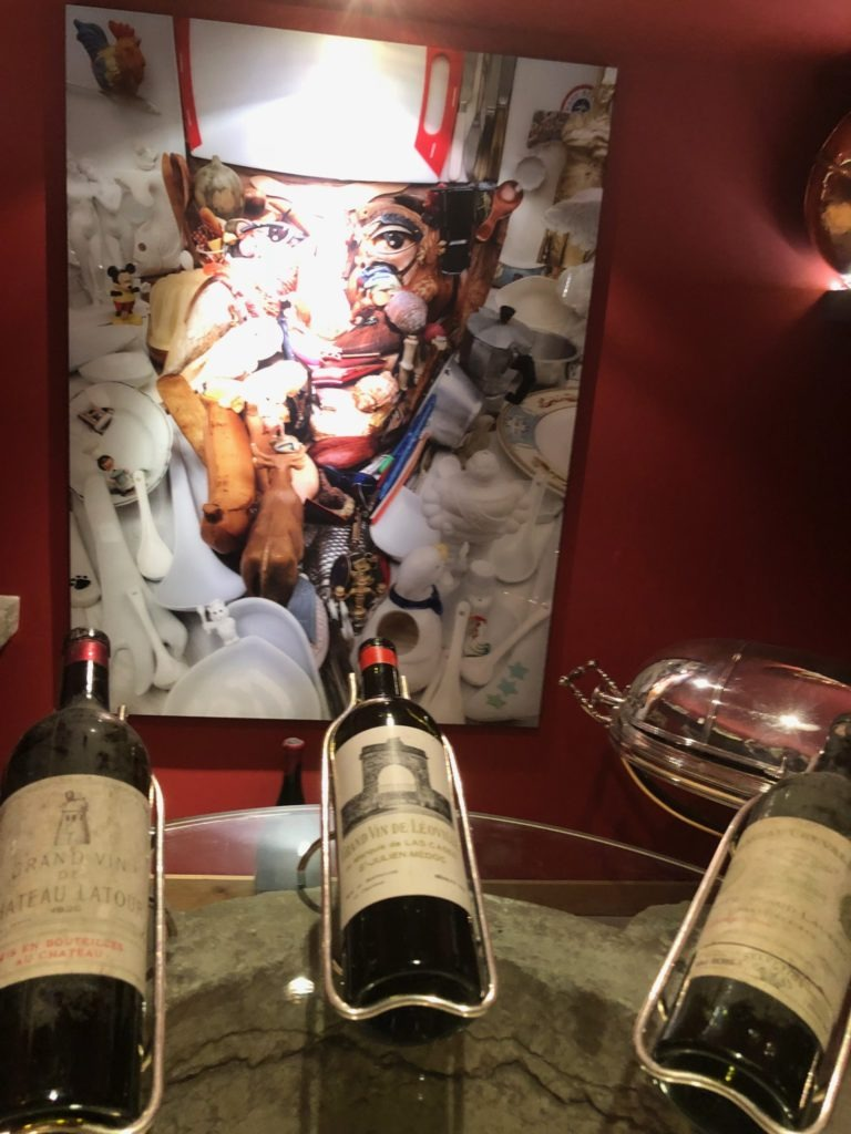 Three wine bottles in the cellar with a mural of Paul Bocuse