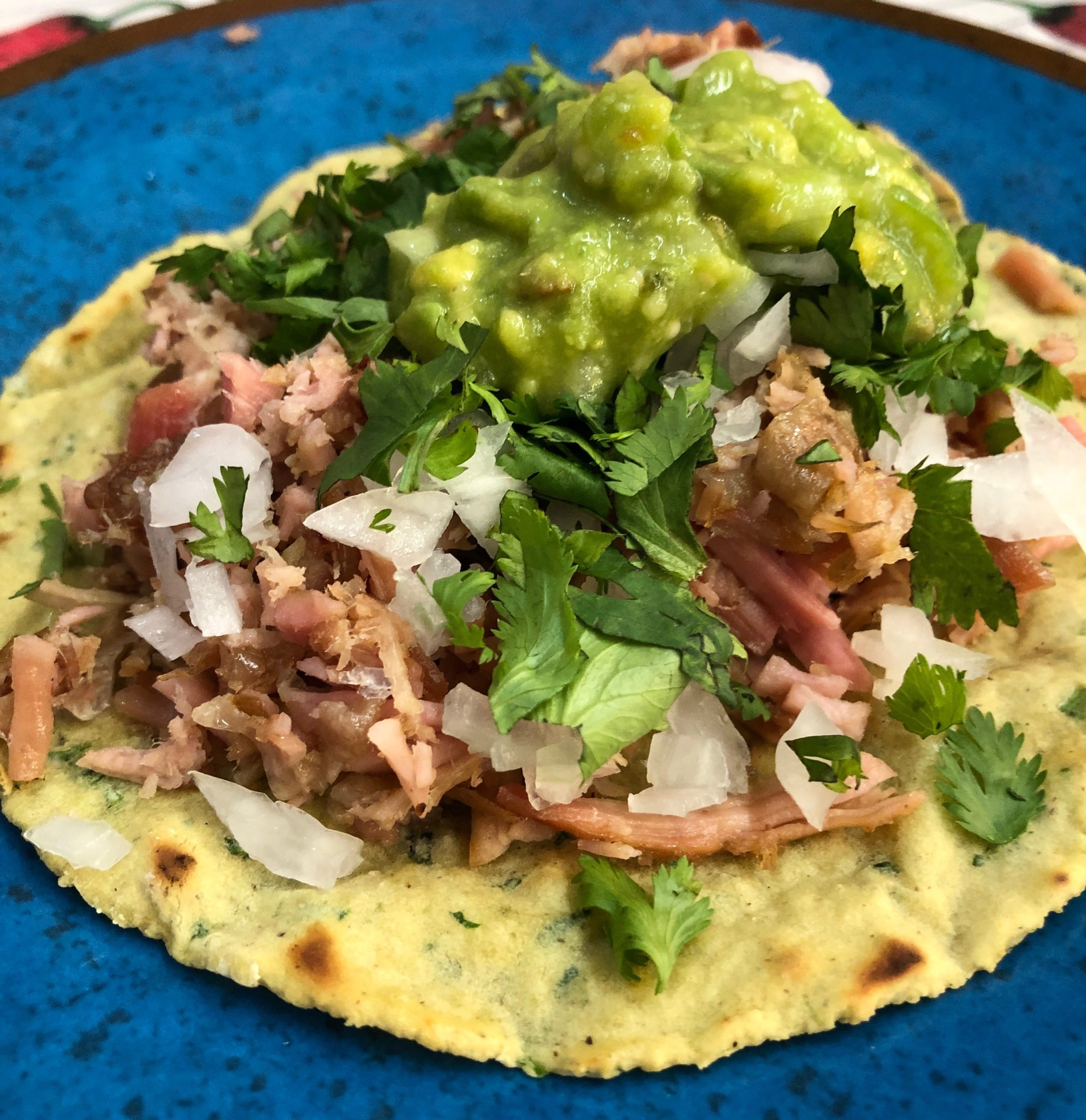 Carnitas taco with guacamole on a blue plate